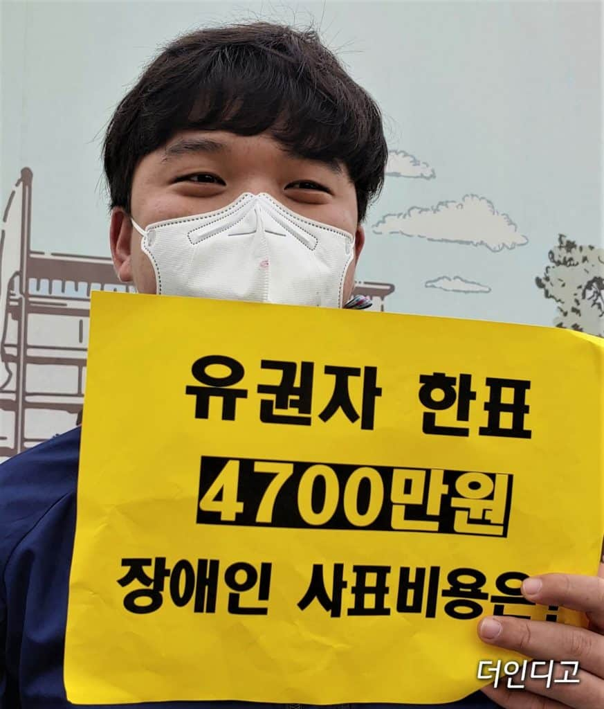 ▲김대범 피플퍼스트 서울센터 활동가가 유권자 한표 4700만원이라고 적힌 손피켓을 들고 있다. ⓒ더인디고