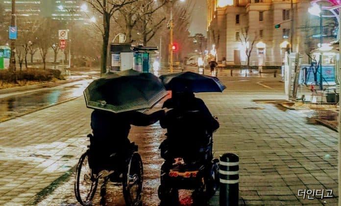 춥고 비오는 날, 우산을 쓰고 전동과 수동휠체어가 나란히 함께 가고 있다 / 사진 = 더인디고