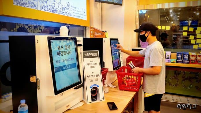 무인 매장에서 한 학생이 키오스크를 이용하여 계산하고 있다
