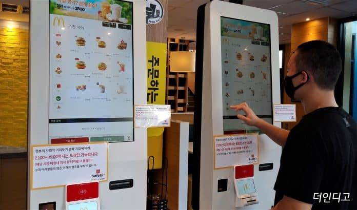 한 학생이 패스트푸드 점에서 햄버거를 키오스크로 주문하고 있다.