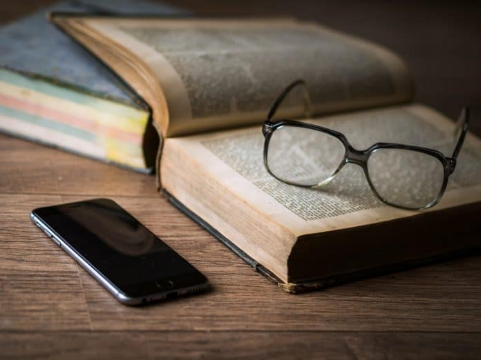책 위에 안경이, 그 옆에 휴대폰이 있다.