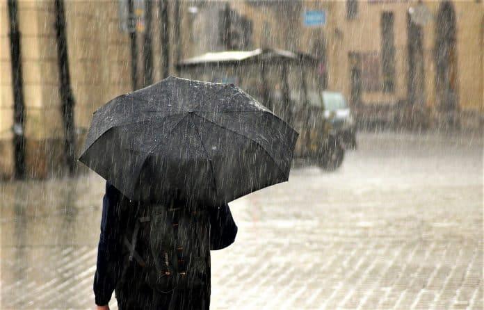 비 오는 날에 검정색 우산을 든 사람이 걸어가고 있다.