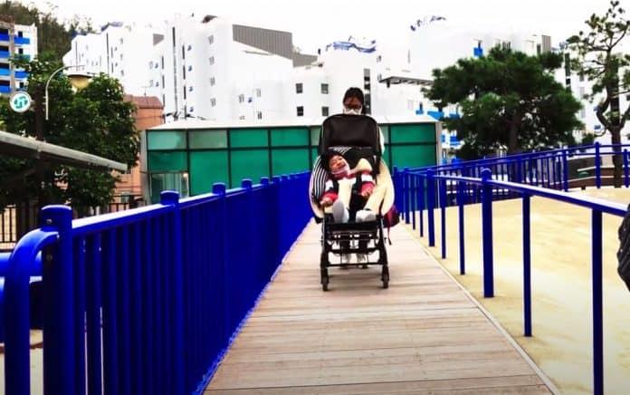 통합놀이터 홍박공원에서 미끄럼틀로 올라가는 경사로에서 휠체어에 앉은 아이를 밀어 주는 서경숙 강사