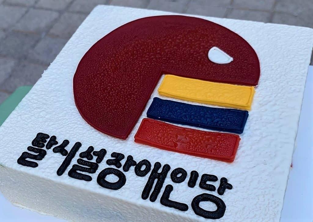 ▲탈시설장애인당 로고가 새겨진 케이크. 노란색을 상징하는 정의당, 파란색의 더불어민주당, 빨간색의 국민의힘을 탈시설장애인당이 먹는 것을 상징했다. 사진=전국장애인차별철폐연대